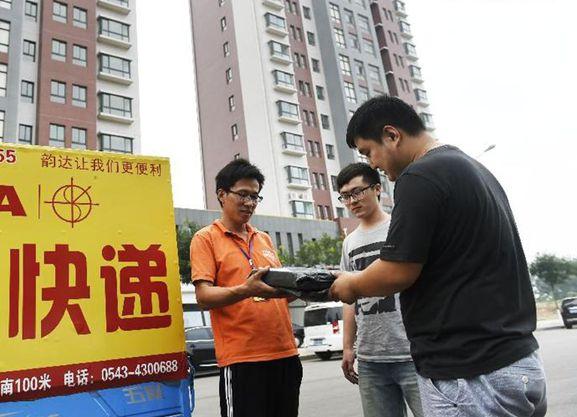 刘钊(中)和孙文泰在ca88亚洲城官网园通过快递为顾客发货