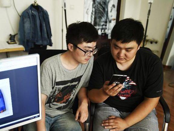 孙文泰(右)和刘钊在工作室查看推送的微店信息